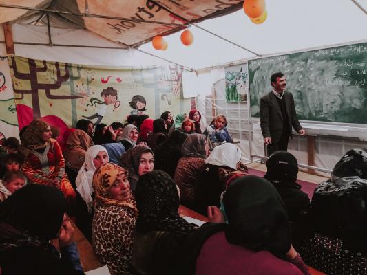 Kinder und Frauen nehmen am Unterricht im Partyzelt teil