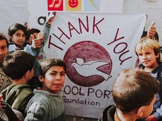 Fluechtlingskinder im Libanon halten ein Danke-Banner fuer die Toolport Foundation